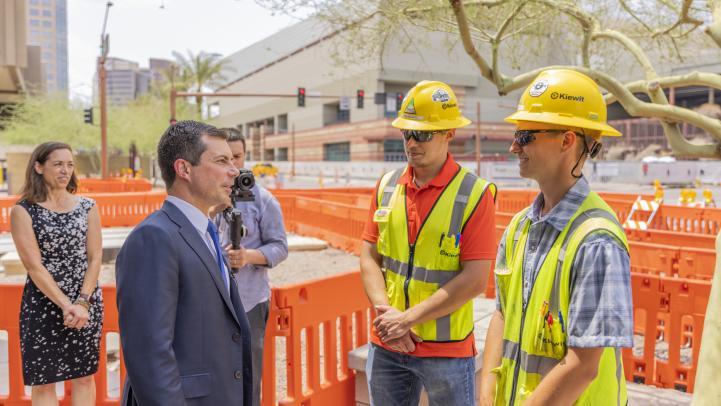 Secretary Buttigieg talks with two construction workers