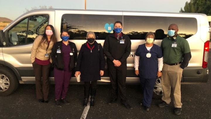 Vanpool riders in masks standing outside of a Valley Metro van.