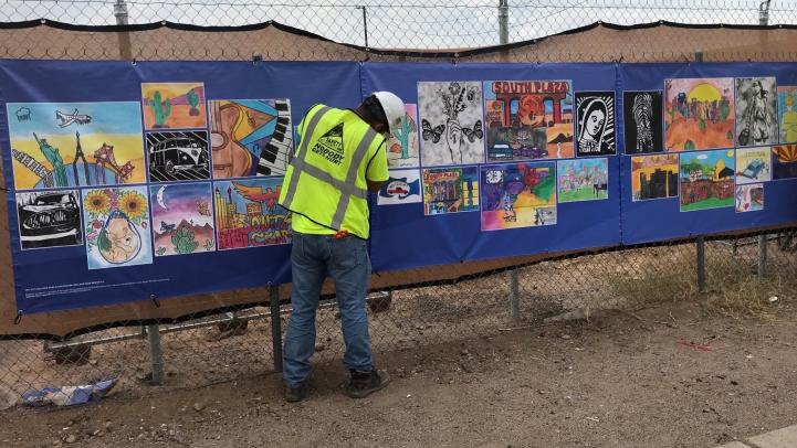 Construction worker hanging student artwork banner on fencing along Central Ave