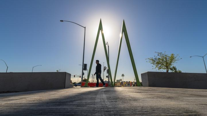 Man walking by light rail station silhouetted by sun