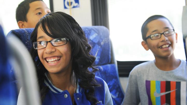 Smiling children riding a bus.