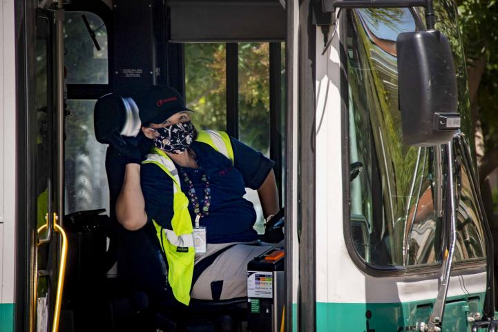 Bus operator wearing mask waves out the window