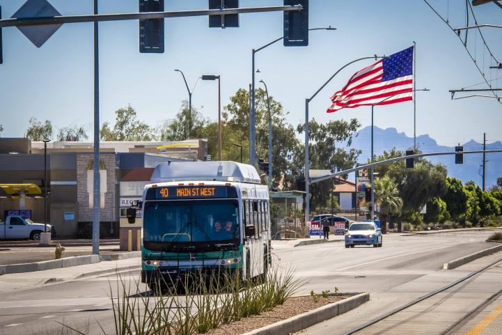 american flag flying over bus driving down street