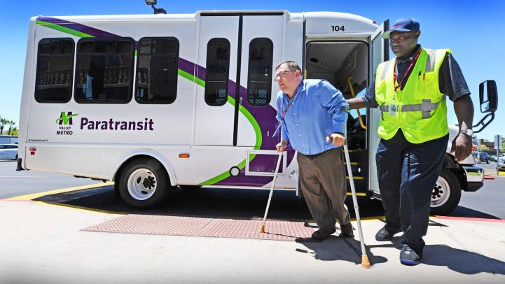 Paratransit driver assisting customer