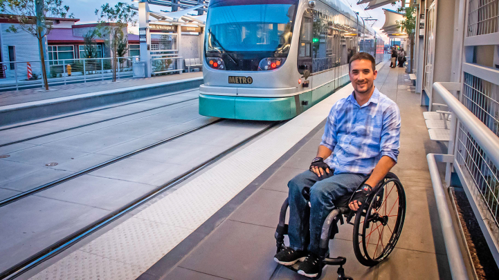 Man in wheelchair on platform as train approaches