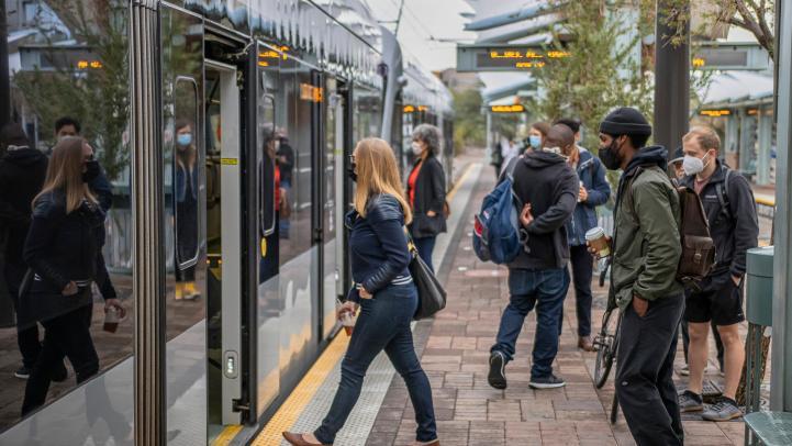 riders wearing face masks enter light rail train
