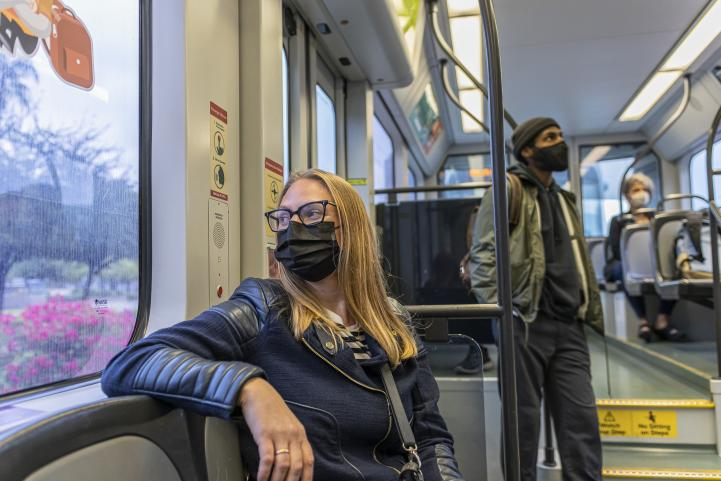 light rail passengers wearing face masks