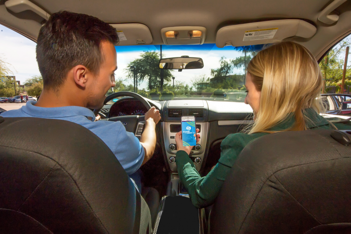 Two people in a carpool looking at the ShareTheRide app on a phone