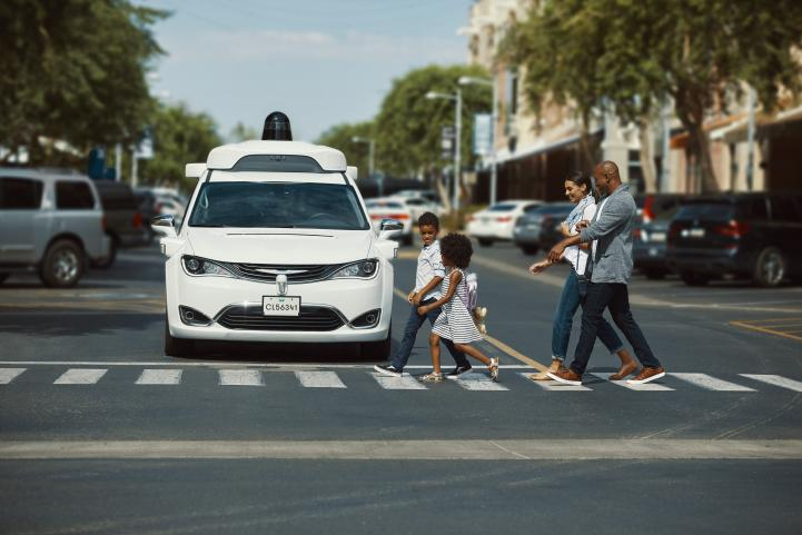 Waymo vehicle in a downtown setting with pedestrians crossing the street