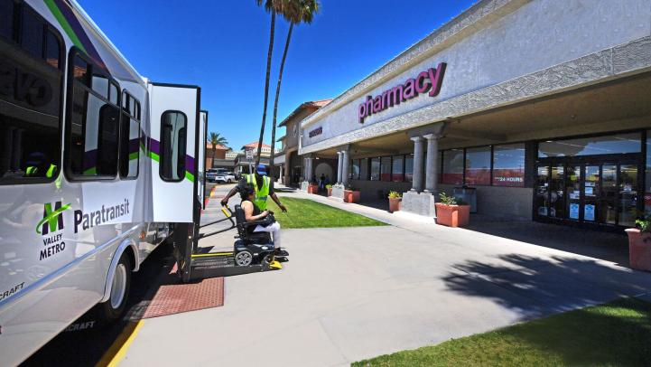 woman in wheelchair helped by operator into the pharmacy