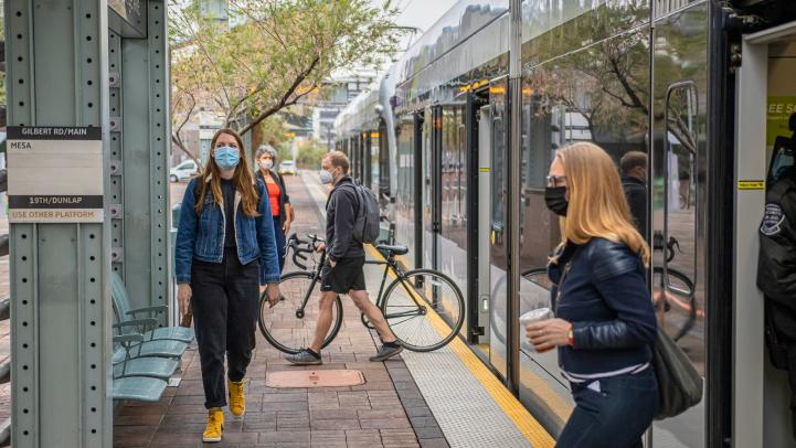 passengers with face masks waiting for light rail