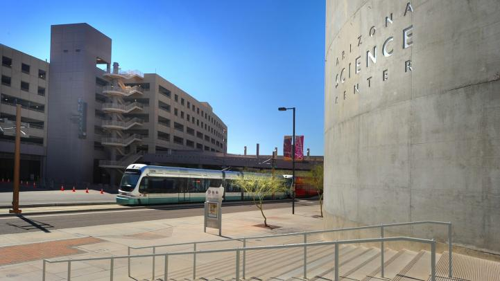Light rail train rides by the arizona science center