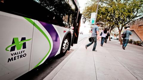 riders deboarding bus with Valley Metro logo showing on side