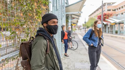 Passengers wearing masks and waiting for a light rail train