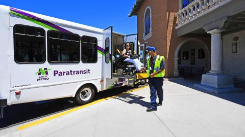 Paratransit rider in wheelchair on vehicle lift helped by operator.