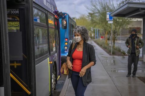 woman wearing mask entering bus through rear door