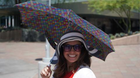 Woman with umbrella, hat, and dazzling smile