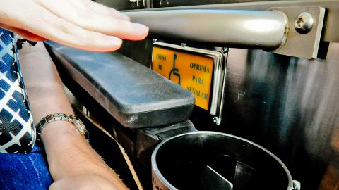 Rider getting ready to push service button aboard bus