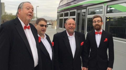 Rob Murray and his barbershop quartet in front of bus.