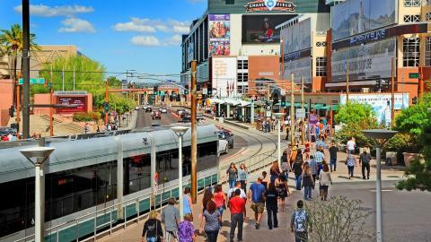 light rail train, people walking, buildings in background