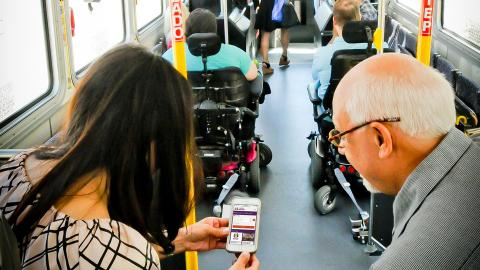 Bus passengers view Valley Metro website on cell phone.