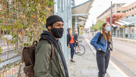 transit riders wear masks waiting for train at light rail station